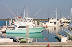 Sportsmans marina. Fishing boats docked at marina with sailboat masts in background Stock Photos
