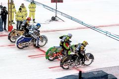Sportsmans que se prepara para competir con en la motocicleta que compite con en el hielo Foto de archivo libre de regalías