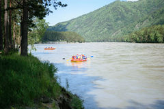 Sportsmans sail on the river on an orange inflatable boat Royalty Free Stock Photo