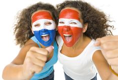 Sportsmanship. Young, screaming Austrian and  Dutch or Paraguayan sport's fans with painted flags on faces and with clenched fists. Front view. Looking at camera Stock Photo