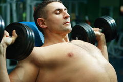 Sportsmen. The young man with a well-muscled body poses and shows the sports body Royalty Free Stock Images