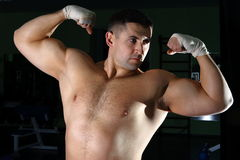 Sportsmen. The young man with a well-muscled body poses and shows the sports body Royalty Free Stock Photos