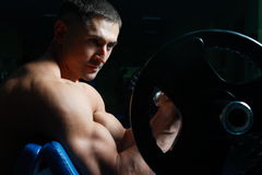 Sportsmen. The young man of a sports constitution is engaged in athletic gymnastics in a hall Royalty Free Stock Image