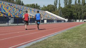 Sportsmen of athletic team training, running on sports field, marathon race stock video footage