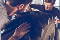 Sportsmen exercising with big tire at gym workout Royalty Free Stock Photography