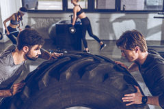 Sportsmen exercising with big tire at gym workout Royalty Free Stock Photos