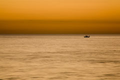 Sportsmen Fishing at Sunset. Sportsmen Fishing on a Boat at Sunset stock photos