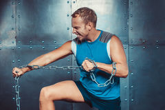 Sportsmen. fit male stands and tear metal chain , concept crossfit fitness workout strenght power. Royalty Free Stock Photos