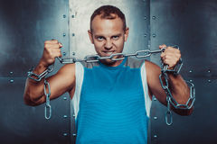 Sportsmen. fit male stands and tear metal chain , concept fitness workout strenght power Stock Photos