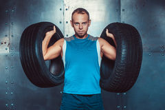 Sportsmen. fit male trainer man keeps the car tires, concept  fitness workout strenght power. Royalty Free Stock Photo