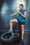 Sportsmen. fit malestands with one foot on the tire iron chain and tears , concept crossfit fitness workout strenght power Royalty Free Stock Photos