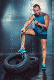 Sportsmen. fit malestands with one foot on the tire iron chain and tears , concept fitness workout strenght power. Royalty Free Stock Images