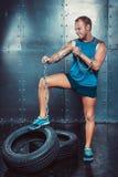 sportsmen geeignete malestands mit einem Fuß auf der Reifeneisenkette und den Rissen, Konzept crossfit Eignungstrainings-Stärkeen Lizenzfreie Stockfotos
