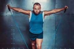 sportsmen geeigneter männlicher Trainermann, der Übungen mit Expandern, Konzept crossfit Eignungstrainings-Stärkemacht tut Lizenzfreie Stockfotografie