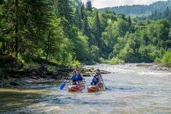Sportsmen go on a mountain river. DZEMBRONYA, UKRAINE - JULY 06, 2016:  Sportsmen go on a mountain river in the Carpathian mountains Royalty Free Stock Photo
