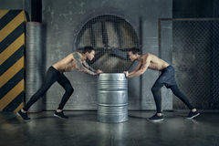 Sportsmen guys are working out with metallic barrel. Perfect fit guys posing and working out Stock Photo
