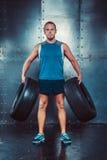 sportsmen l'uomo maschio adatto dell'istruttore tiene le gomme di automobile, potere di forza di allenamento di forma fisica del  Fotografie Stock