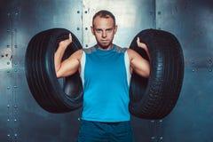 sportsmen l'uomo maschio adatto dell'istruttore tiene le gomme di automobile, potere di forza di allenamento di forma fisica di c Fotografia Stock Libera da Diritti