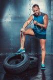 sportsmen malestands aptos com um pé na corrente do ferro de pneu e nos rasgos, poder da força do exercício da aptidão do conceit imagens de stock royalty free