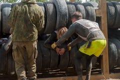 Sportsmen move between old tires. Tyumen Stock Photos