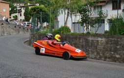 Sportsmen in orange wooden racing car competing to win in Lecco district. Royalty Free Stock Images