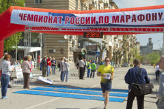 Sportsmen participants of the Volgograd marathon run through the finish line Stock Images