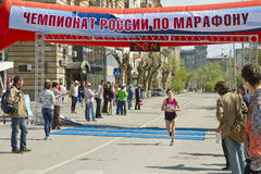 Sportsmen participants of the Volgograd marathon run through the finish line Stock Photos