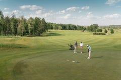 Sportsmen playing golf on green fairway at daytime Stock Image