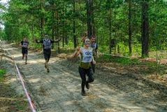 Sportsmen run between stages in extrim race.Tyumen Royalty Free Stock Image