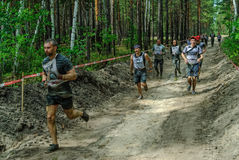 Sportsmen run between stages in extrim race.Tyumen Royalty Free Stock Images