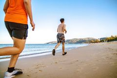 Sportsmen in sneakers running along summer beach. fitness, sport and technology concept. stock photography