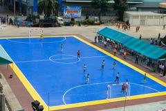 Sportsmen train on blue stadium. BANGKOK, THAILAND - 21 NOV 2013: Sportsmen train on blue outdoor stadium in front of sport science bureau of Sports Authority of Royalty Free Stock Photo