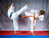 Sportsmen are training blows legs on the mat Royalty Free Stock Image