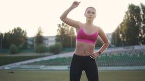 Sportsmenka grże up przed trenować w zmierzchu dziewczyna w sportach odziewa robić rozciąganiu przed biegać przez zdjęcie wideo