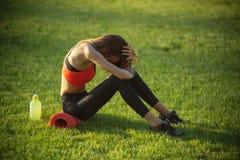 Sportsmenka siedzi na zielonej trawie z gym wyposażeniem na lecie obrazy stock
