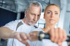 Sportsmenki i seniora trenera szkolenie z dumbbells w centrum sportowym obrazy royalty free