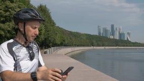Sportswear ατόμων που οδηγά ένα κράνος ποδηλάτων στηρίζεται σε έναν όμορφο περίπατο πόλεων απόθεμα βίντεο