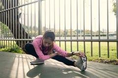 Sportswear моды девушки спорта фитнеса делая тренировку фитнеса йоги в улице Подходящая молодая азиатская женщина делая разминку  Стоковая Фотография RF