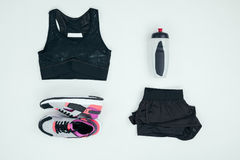 Sportswear com a garrafa das sapatilhas e dos esportes isolada no cinza foto de stock royalty free