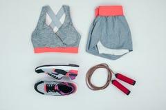 Sportswear com sapatilhas e corda de salto isolada no cinza fotos de stock