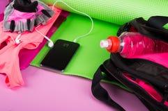 Sportswear cor-de-rosa, acessórios da aptidão, tapete do cal e uma garrafa da água em um saco, em um fundo cor-de-rosa foto de stock royalty free