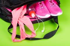 Sportswear e acessórios cor-de-rosa para a aptidão, em um saco em uma luz - fundo verde fotografia de stock royalty free