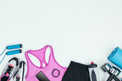 Sportswear with sneakers, smartphone, fitness tracker and fitness equipment. Isolated on grey Stock Photography