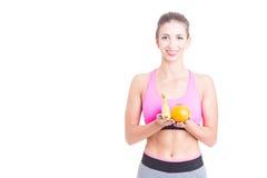 Sportswear vestindo da jovem mulher no gym que guarda frutos imagem de stock royalty free