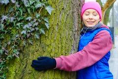 Sportswear vestindo da mulher que abraça a árvore fotografia de stock royalty free