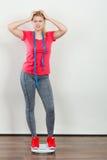 Sportswear vestindo da mulher que está na máquina do peso imagens de stock