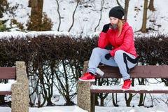Sportswear vestindo da mulher que senta-se fora durante o inverno Fotografia de Stock