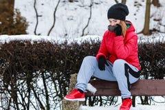 Sportswear vestindo da mulher que senta-se fora durante o inverno Fotos de Stock
