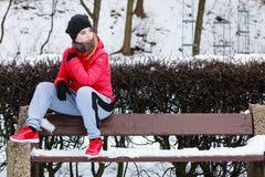 Sportswear vestindo da mulher que senta-se fora durante o inverno Fotos de Stock Royalty Free