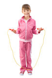 Sportswoman. The little girl in a pink sports suit jumps through a jumping rope Stock Photo